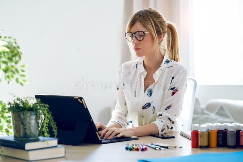 Koncentrerad härlig ung märkes- kvinna som arbetar med hennes digitala minnestavla på kontoret arkivfoto