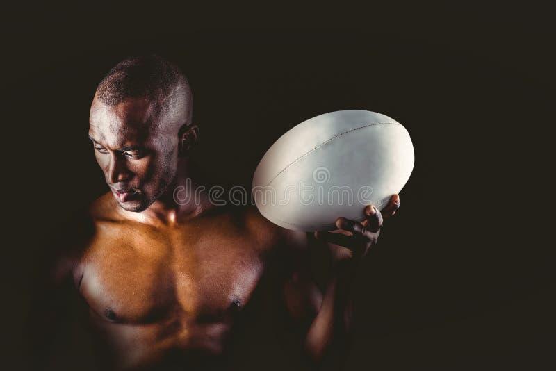Koncentrerad hållande rugbyboll för shirtless idrottsman royaltyfria foton