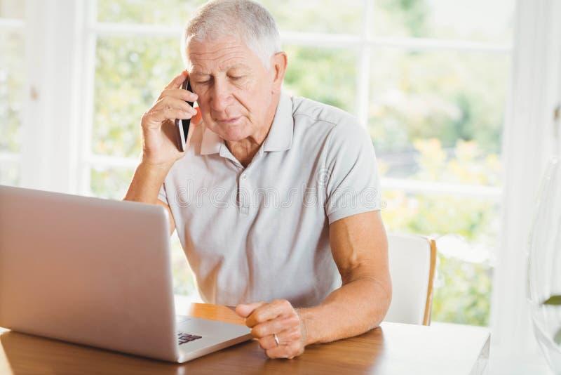 Koncentrerad hög man som ser för bärbar dator och telefon att kalla royaltyfria foton