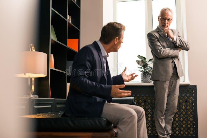 Koncentrerad hög psykolog som uppmärksamt lyssnar till hans patient arkivbild