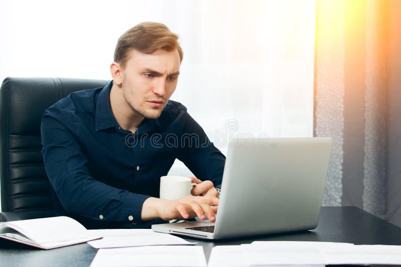 Koncentrerad journalist som gör en artikel med kaffe i hand royaltyfri fotografi