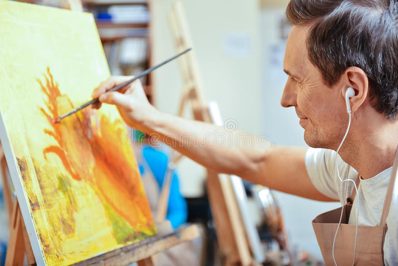 Koncentrerad konstnär som målar en bild i hemtrevlig studio arkivbilder
