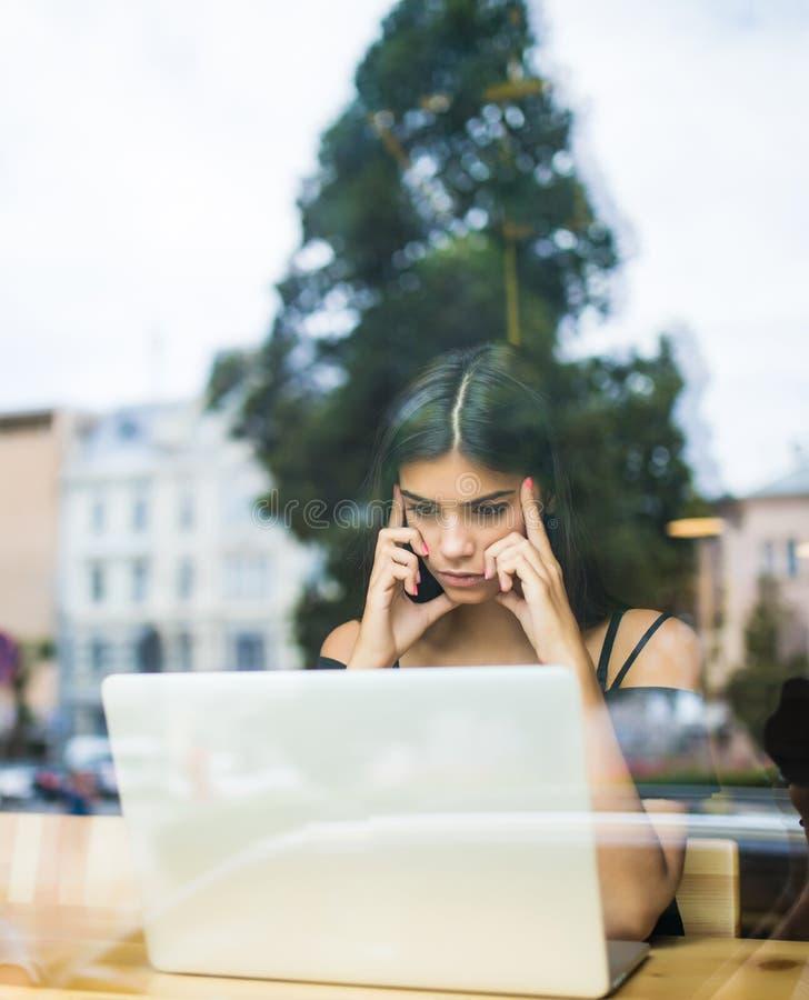 Koncentrerad kvinna som arbetar på en dator på ett kafé medan blick till och med fönsterexponeringsglaset royaltyfria foton
