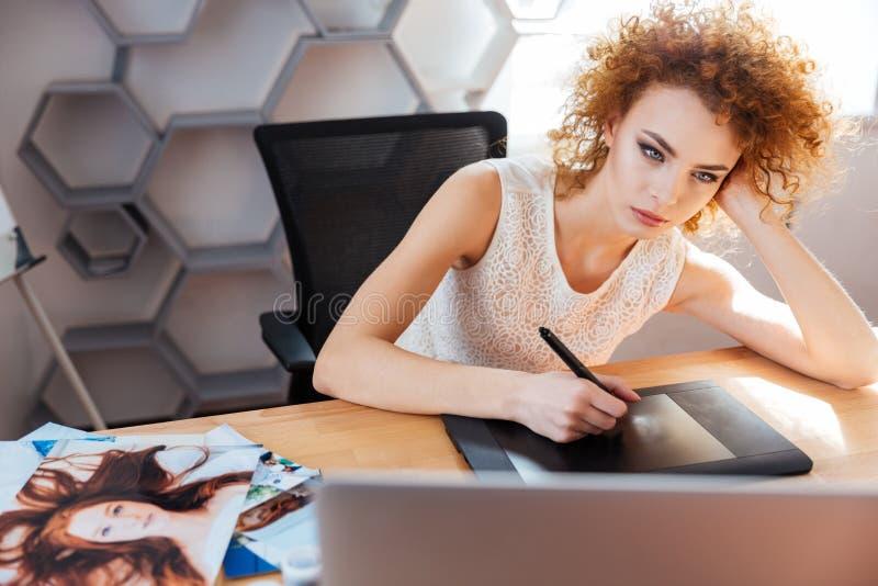 Koncentrerad kvinnafotograf som bearbetar bilder genom att använda den grafiska minnestavlan i regeringsställning fotografering för bildbyråer