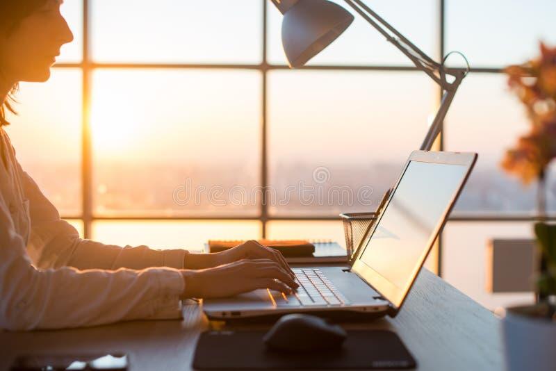 Koncentrerad kvinnlig anställdmaskinskrivning på arbetsplatsen genom att använda datoren Stående för sidosikt av en copywriter so arkivfoto