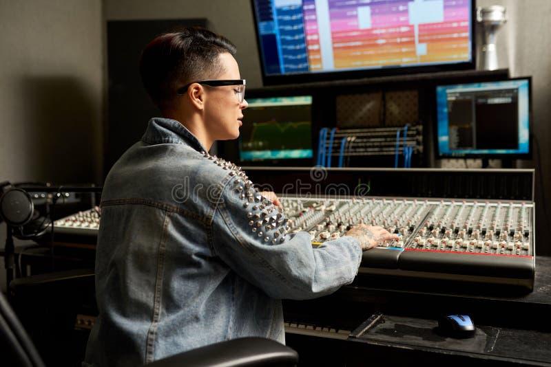 Koncentrerad ljudsignal tekniker som justerar blandaren i studio arkivfoto