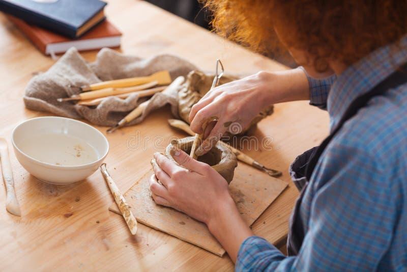 Koncentrerad lockig ung kvinna som arbetar på lerakrukan fotografering för bildbyråer