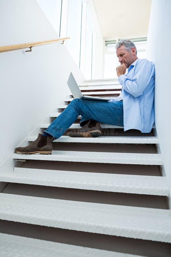 Koncentrerad man som använder bärbara datorn på moment royaltyfri bild