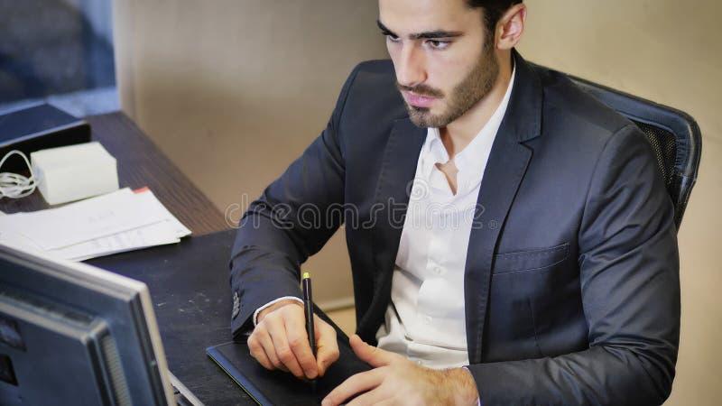 Koncentrerad man som i regeringsställning använder den grafiska minnestavlan arkivfoton