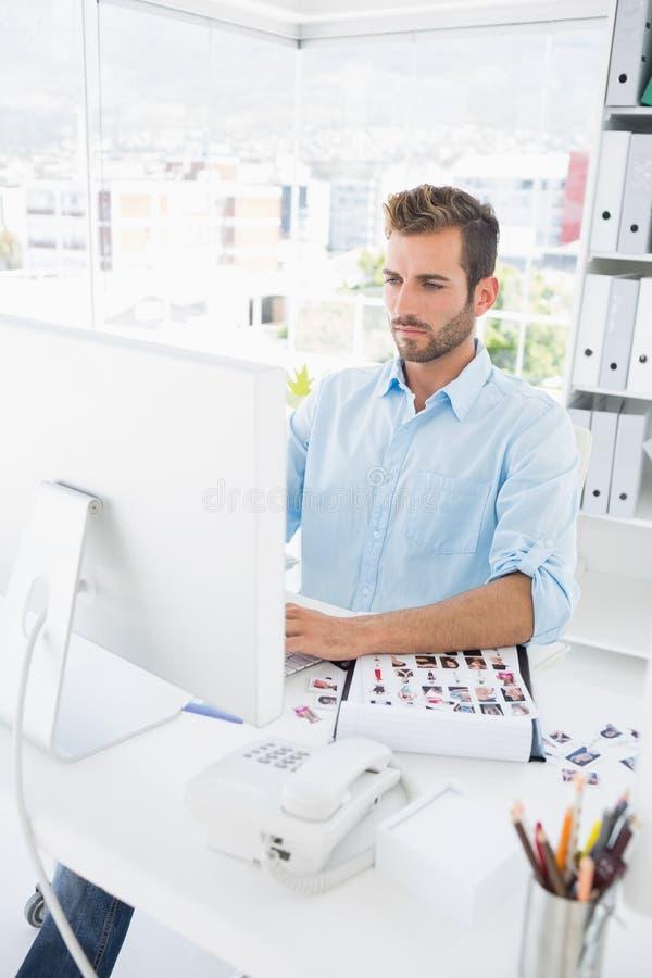 Koncentrerad manlig fotoredaktör som arbetar på datoren fotografering för bildbyråer
