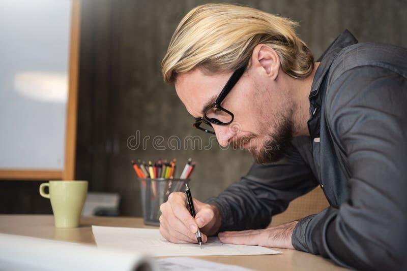 Koncentrerad manlig idérik teckning på hans arbete arkivfoto