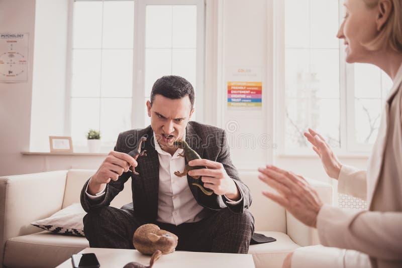 Koncentrerad manlig person för brunett som spelar med leksaker royaltyfri fotografi