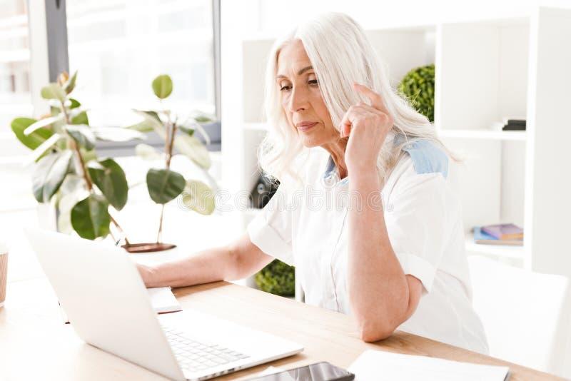 Koncentrerad mogen kvinna som inomhus i regeringsställning sitter royaltyfri foto