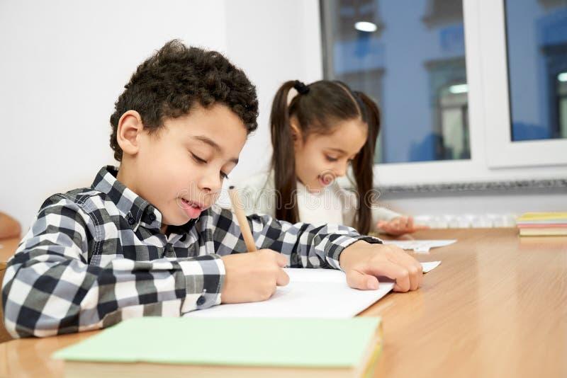 Koncentrerad pojke som sitter på tabellen och skriver i förskriftsbok royaltyfri foto