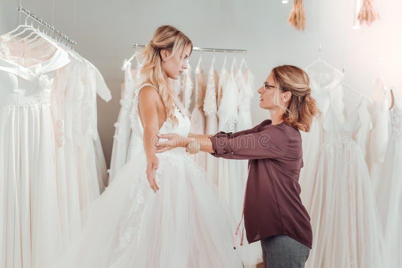 Koncentrerad skräddare som skapar en klänning för en brud royaltyfria bilder