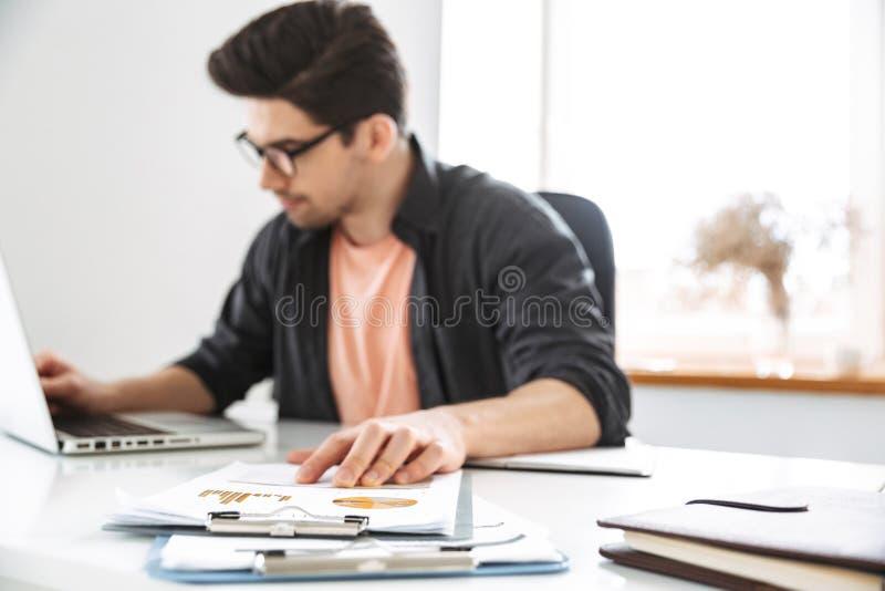 Koncentrerad stilig man i glasögon som arbetar med bärbar datordatoren royaltyfria bilder