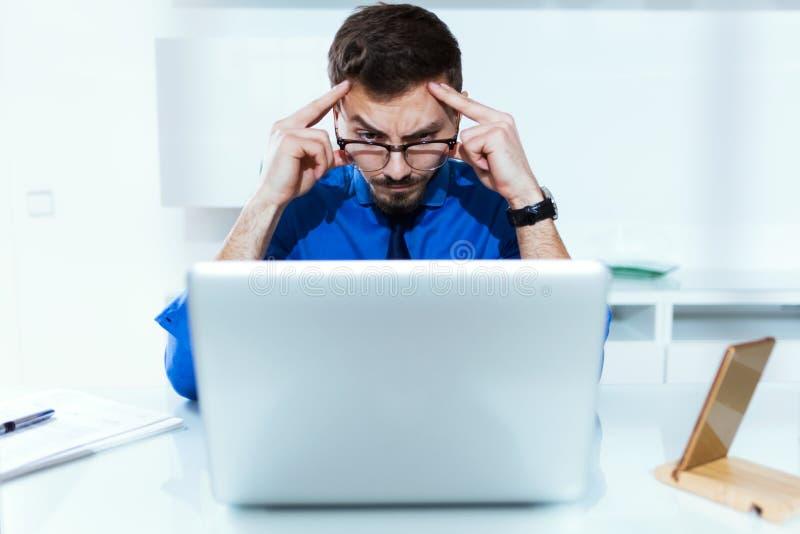Koncentrerad stilig ung affärsman, medan arbeta med bärbara datorn i kontoret arkivfoton