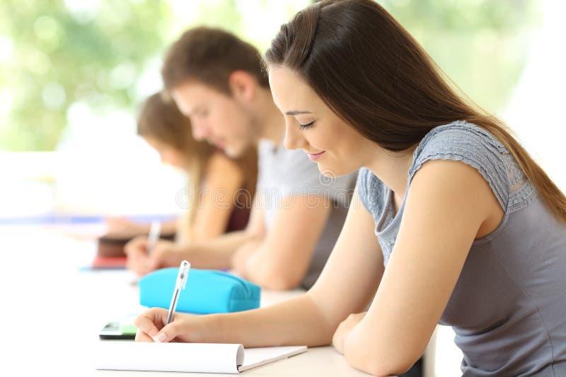 Koncentrerad student som tar anmärkningar i ett klassrum arkivfoto