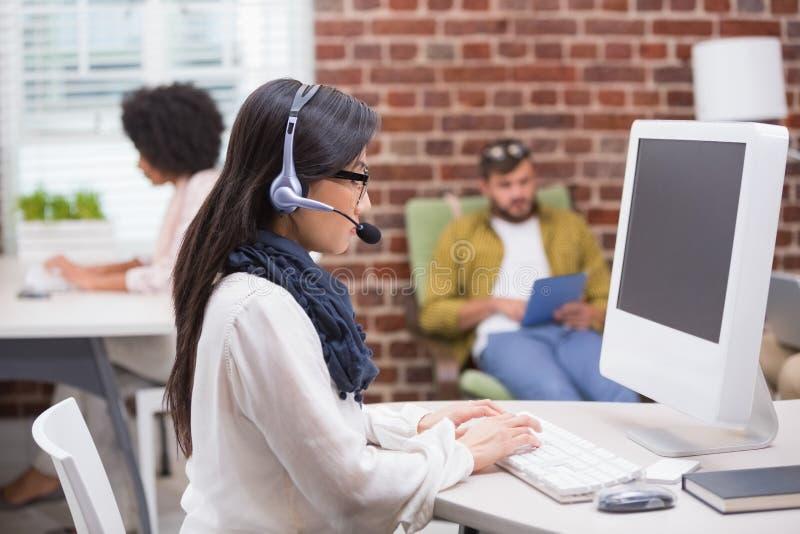 Koncentrerad tillfällig ung kvinna som använder datoren arkivfoto