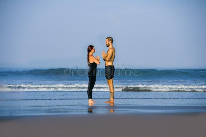 Koncentrerad ung övning för acroyoga för attraktiva och härliga akrobatpar övande hålla practiing yoga för jämvikt på arkivbild