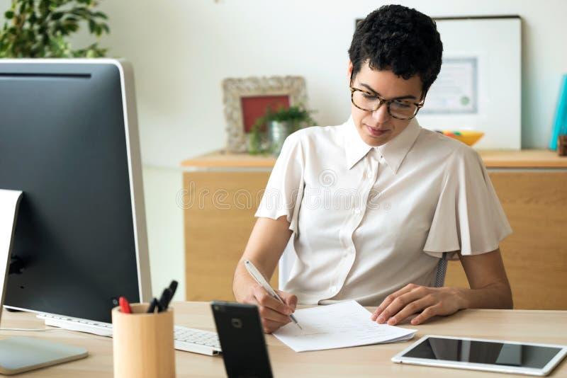 Koncentrerad ung affärskvinna som arbetar på skrivbordet i kontoret royaltyfri foto