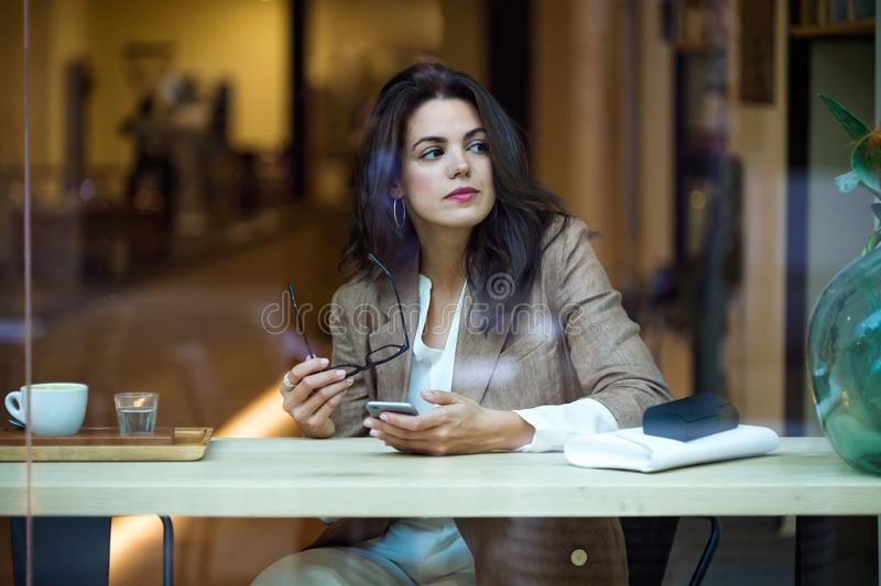 Koncentrerad ung affärskvinna som smsar med hennes mobiltelefon i coffee shop royaltyfri fotografi