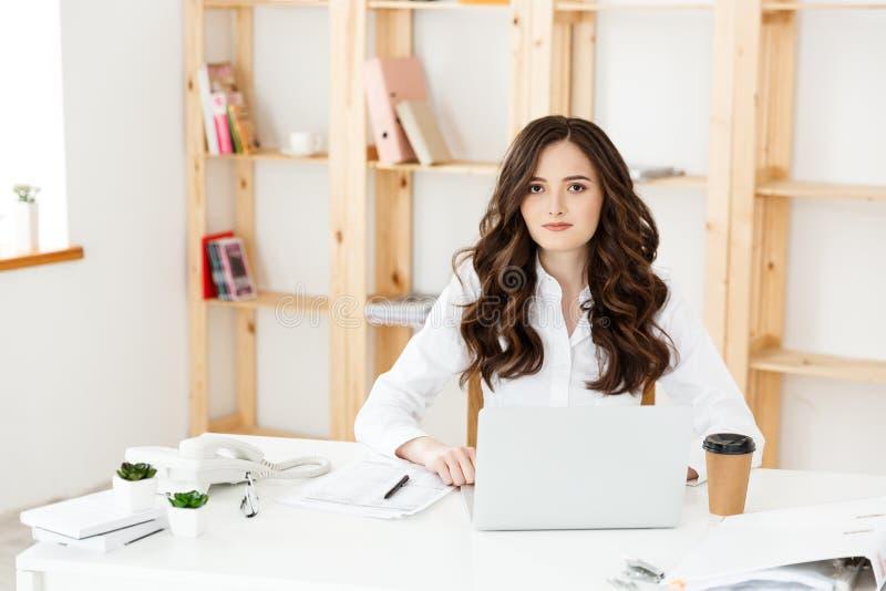 Koncentrerad ung härlig affärskvinna som arbetar på bärbara datorn i ljust modernt kontor royaltyfri fotografi