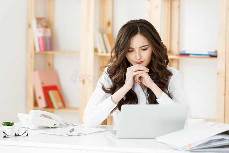 Koncentrerad ung härlig affärskvinna som arbetar på bärbara datorn i ljust modernt kontor royaltyfria bilder