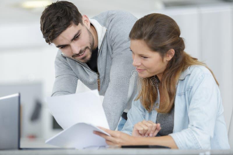 Koncentrerad ung man och kvinna som hemma arbetar royaltyfri foto