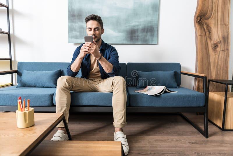 Koncentrerad ungdomlig skäggig grabb som använder hans smarta telefon i lägenhet royaltyfri bild