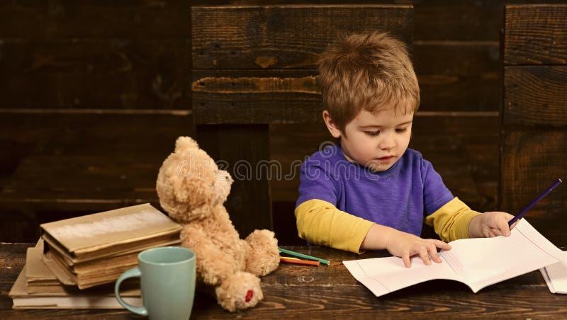 Koncentrerad ungehandstil i förskriftsbok Förskole- pojkesammanträde på skrivbordet Lära bokstäver i dagis royaltyfria foton