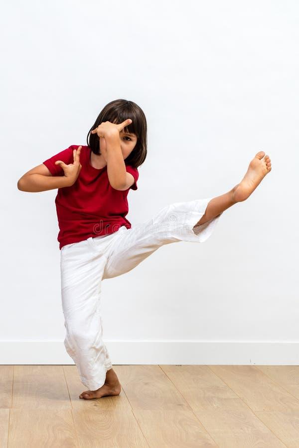 Koncentrerad ungt barnvisningnåd med stridighet lägger benen på ryggen och armar arkivbild