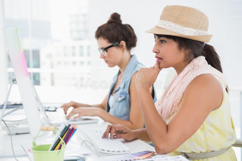 Koncentrerade kollegor som skriver på tangentbordet arkivfoton