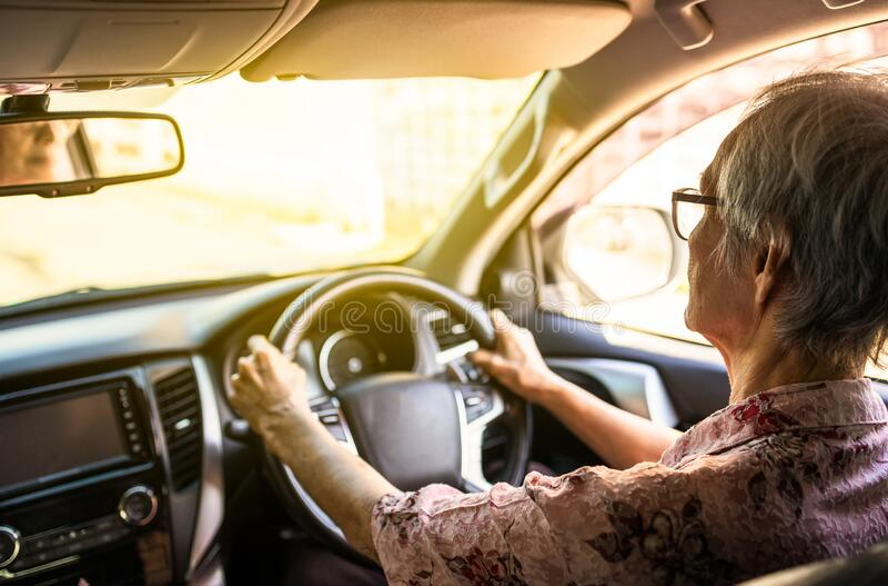 Koncentrerade kvinnliga förare håller ratten stadig med långsam hastighet för att undvika olyckor, och äldre personer som kör bil arkivfoton