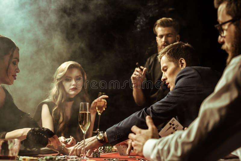 Koncentrerade män och kvinnor som spelar poker i kasino royaltyfria bilder