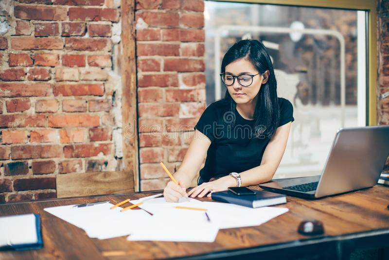 Koncentrerat på arbete Säker ung kvinna i tillfälliga kläder som arbetar på bärbara datorn, medan sitta nära fönster i idérikt ko royaltyfri bild