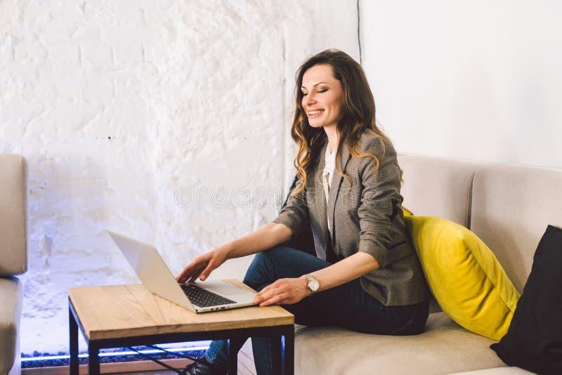 Koncentrerat p? arbete Säker ung vuxen medelålders kvinna i smart tillfällig kläder och att arbeta på en bärbar dator som sitter arkivfoto