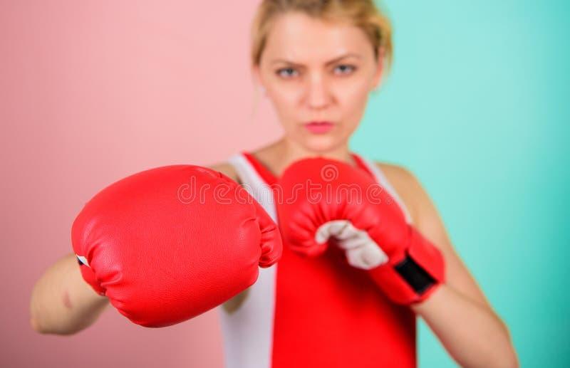 Koncentrerat p? stansmaskin Kvinnaboxninghandskar som fokuseras p? attack Ambiti?sa handskar f?r flickakampboxning Kvinnliga r?tt arkivbild