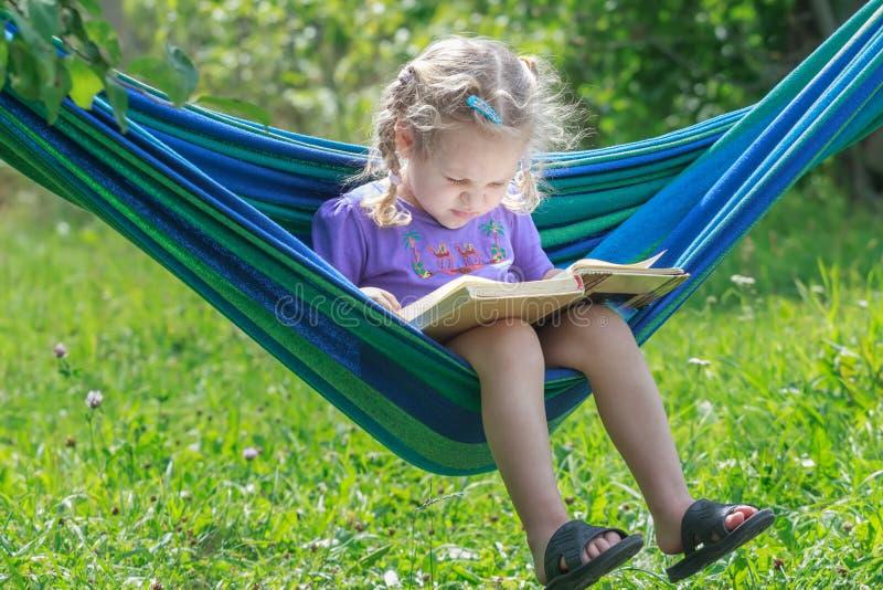 Koncentrerat två år gammal flickaläsning öppnade boken på den hängande hängmattan i grön sommarträdgård utomhus royaltyfri fotografi