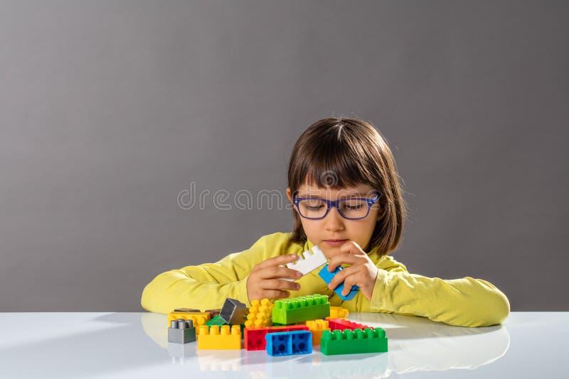 Koncentrerat ungt barn som spelar med byggnadskvarter och karriärteknikern fotografering för bildbyråer