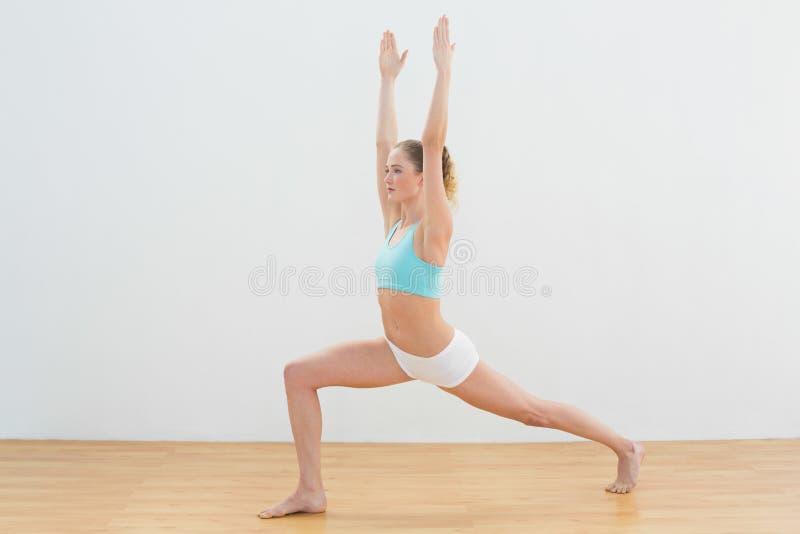 Koncentrować szczupłą blondynki pozycję w wysokiej lunge pozie fotografia stock