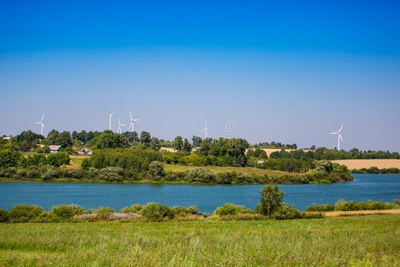 koncepcja ekologii obraz?w wi?cej mojego portfolio Silniki wiatrowi blisko błękitnej rzeki krzywy zdjęcia stock