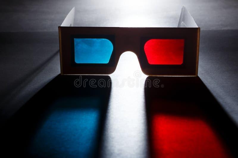 Koncepcja filmu w kinie Okulary 3D z soczewkami czerwonymi i niebieskimi z miękkim kolorowym cieniem na ciemnym tle fotografia royalty free