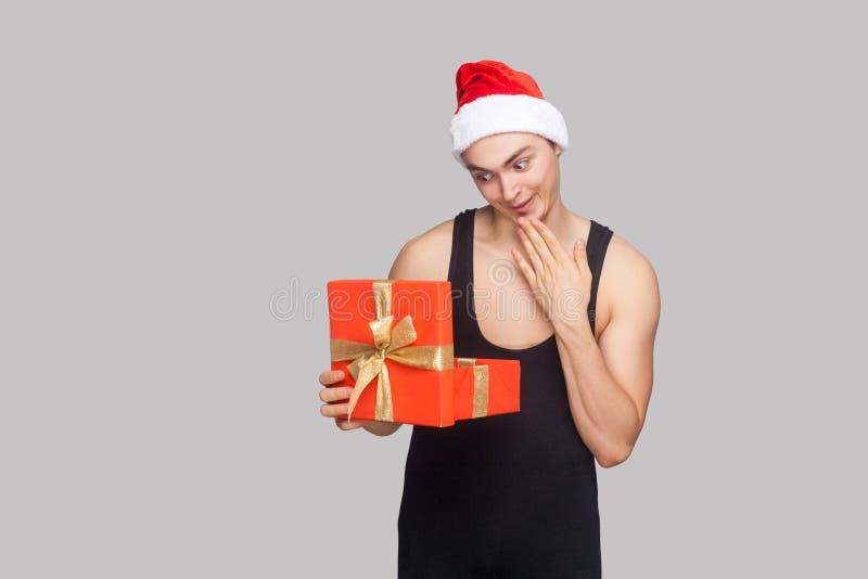 koncepcja nowego roku Mężczyzna w czerwonego kapeluszowego mienia prezenta czerwonym pudełku i lookin zdjęcie royalty free