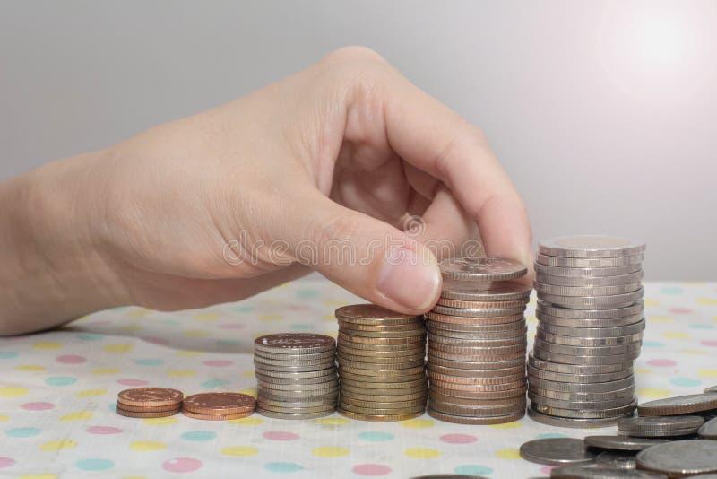 Koncepcja oszczędzania pieniędzy prezentowana przez kobiece dłonie, w której kasy rosną na białe, pieniądze, finanse, biznes fotografia stock
