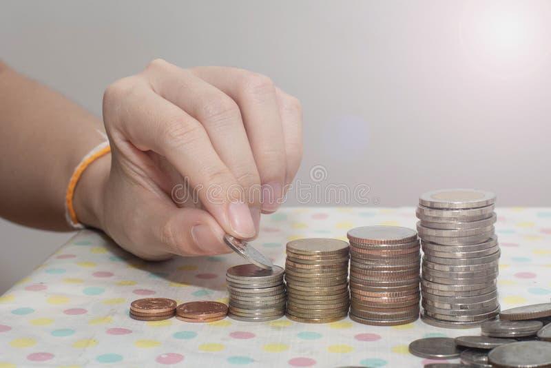 Koncepcja oszczędzania pieniędzy prezentowana przez kobiece dłonie, w której kasy rosną na białe, pieniądze, finanse, biznes obrazy stock