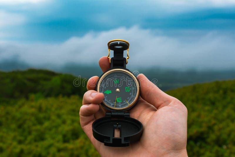 Koncepcja podróżowania, kempingu, orientacji i nawigacji - czarny kompas magnetyczny w dÅ'oni czÅ'owieka, zamazany krajobraz zdjęcie royalty free