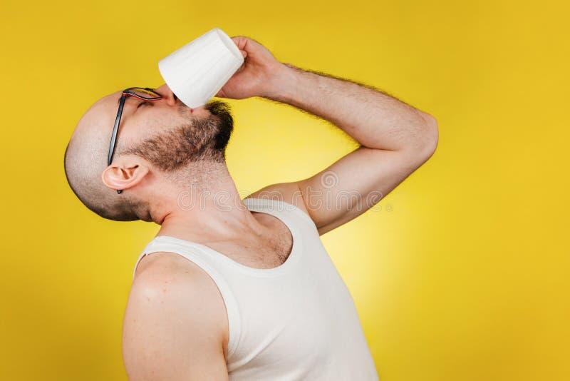 Koncepcja porannego przebudzenia i wydajności Łysy, brodaty mężczyzna z okularami, pijący kubek kawy lub herbaty w jednej łyżeczc fotografia royalty free