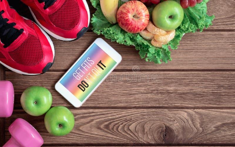 Koncepcja smartfona zakładająca zdrowy styl życia Get Fits Don't Quit on mobile phone with sport buts, dumbbells and zdjęcia stock
