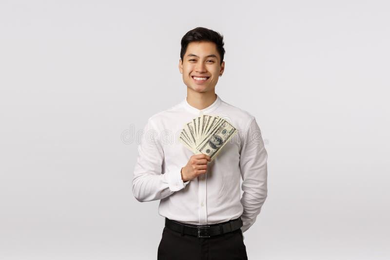 Koncepcja sukcesu, dobrobytu i rekrutacji Zadowolony, przystojny, azjatycki przedsiębiorca zyskuje dużo pieniędzy, przechowując g fotografia stock